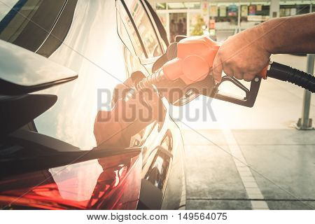 Car refueling on petrol station. Man pumping gasoline fuel in car at gas station.