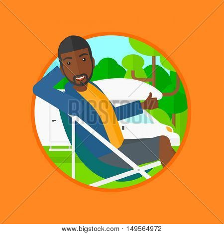 An african-american man sitting in chair and giving thumb up on the background of camper van. Man enjoying vacation in camper van. Vector flat design illustration in the circle isolated on background.