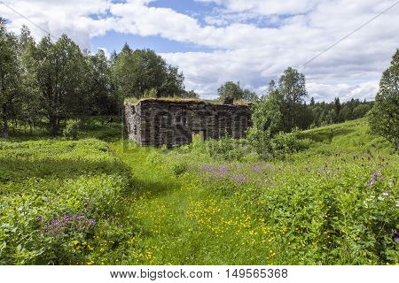 Abandoned buildings, slate stones in rural area. Flowers this side, landscape.