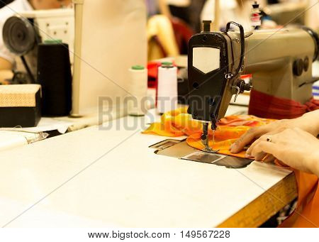 Woman' s hand sewn fabric on old sewing machine in workshop