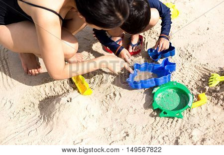 Education mother with son with hand pointing hermit crab playing on the beach