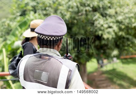 Security guard watching for safty of tourist woman in the forest