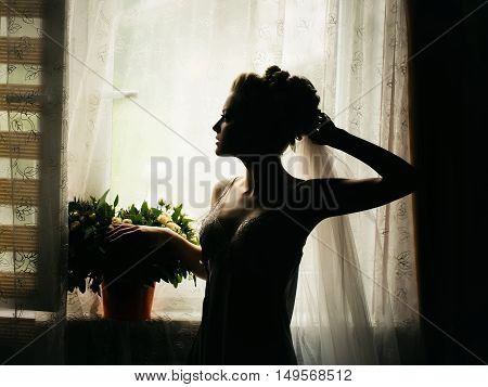 young sexy wedding woman or girl bride silhouette with flowers in stylish blonde hair and on pretty face in nightgown near curtain and bouquet on window