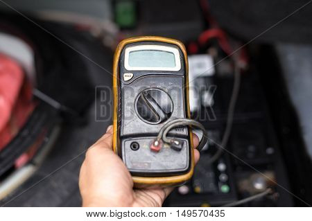 Mechanic checking a car battery level with voltmeter in garage