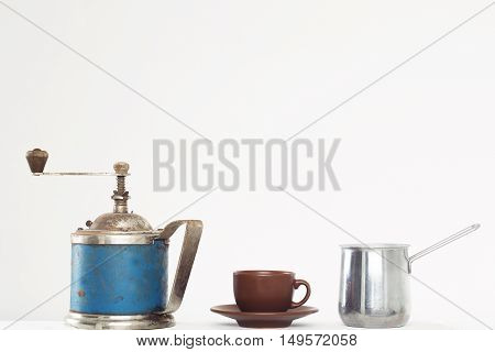 Vintage blue handle coffee grinder brown cup and saucer metal coffeepot kitchenware isolated on white background