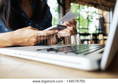 Happy Asia woman doing shopping online and use laptop shopping and find promotion. Business and modern lifestyle concept: Young woman shopping online at coffee shop (selective focus).