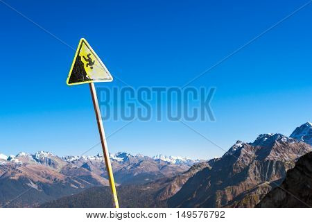 Yellow warning sign about the danger of falling down the slope. Autumn mountain landscape views of hills and peaks of Caucasus mountains. Krasnaya Polyana - Alpine ski resort. Sochi Russia