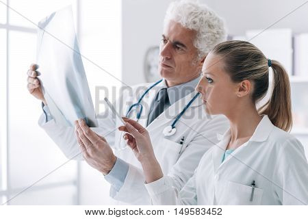 Radiologist Checking An X-ray With His Assistant