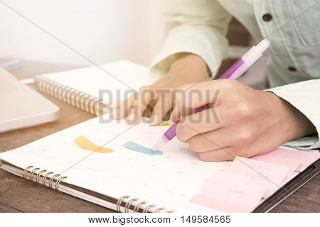 Business women checking appointments in the calendar on desk work at the office.