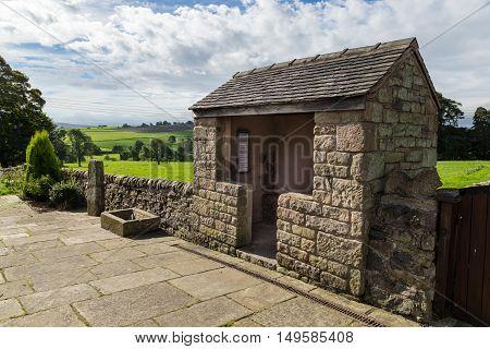 LONGNOR ENGLAND - SEPTEMBER 28: Stone bus shelter on Buxton Road. In Longnor Staffordshire England. On 28th September 2016.