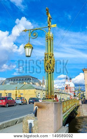SAINT PETERSBURG RUSSIA - APRIL 25 2015: The old scenic streetlight on Panteleimonovsky bridge with the red bell tower of St Panteleimon Church in front on April 25 in Saint Petersburg.