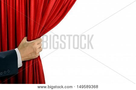 Hand opening stage red curtain over white