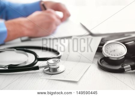 Sphygmomanometer, cardiogram and stethoscope on doctor table, close up view