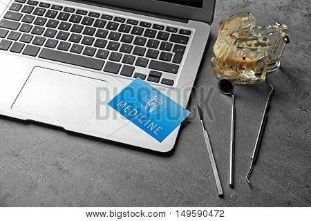 Medical service concept. Visiting card, dental equipment and laptop on grey background