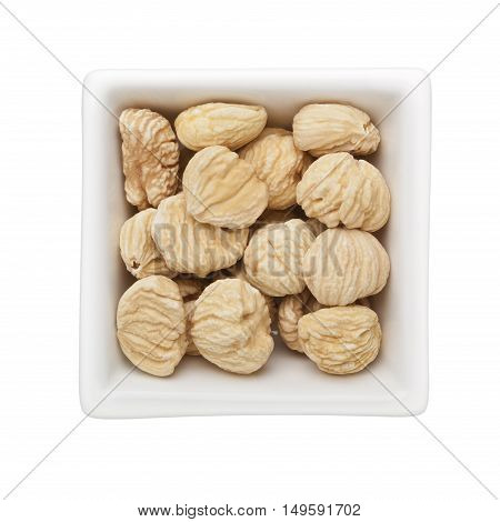 Dried unshelled chestnuts in a square bowl isolated on white background