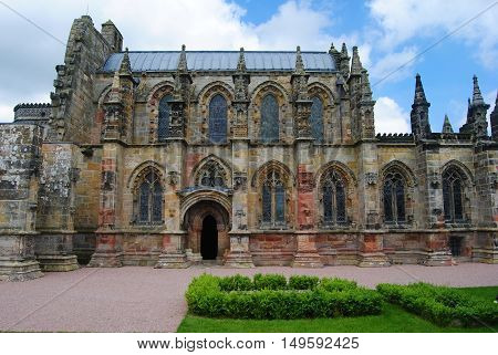 Roslin, United Kingdom - June 18, 2014. Exterior view of Rosslyn Chapel, with grass lawn, on cloudy summer day.