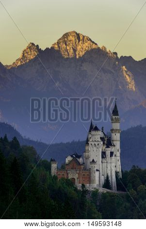 Beautiful morning view of the Neuschwanstein castle with highlighting mountains after sunrise Bavarian Alps Bavaria Germany. Typical alpine scenery.