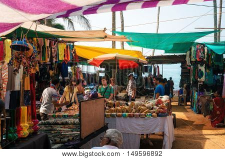 Anjuna Beach Goa India - December 5 2015: Hippie handmade shops and customers at the Wednesday flea market selling varieties of merchandise and souvenirs.