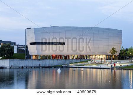 WOLFSBURG GERMANY - SEP 23 2016: Modern Building at the Volkswagen Autostadt illuminated at night. Wolfsburg Germany