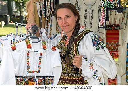 TIMISOARA ROMANIA - SEPTEMBER 24 2016: Romanian woman who sells traditional clothes at a fair called Fair of craftsmen