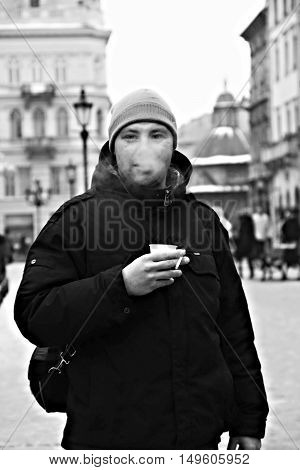 young man exhales smoke and drink coffee.