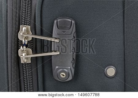 Closeup top view of zipper of fabric suitcase with built in luggage lock, new and clean luggage in black color