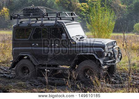 KRASNORECHENSKOYE RUSSIA - SEPTEMBER 24 2016: Black car moving in mud