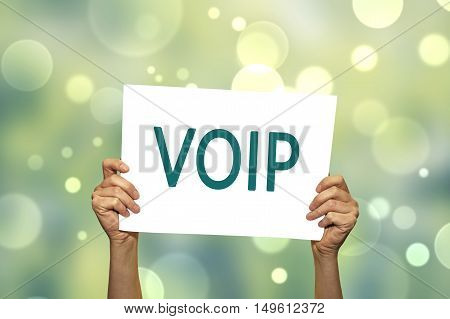 VOIP (voice over internet protocol) card in hand with abstract light background. Selective focus.