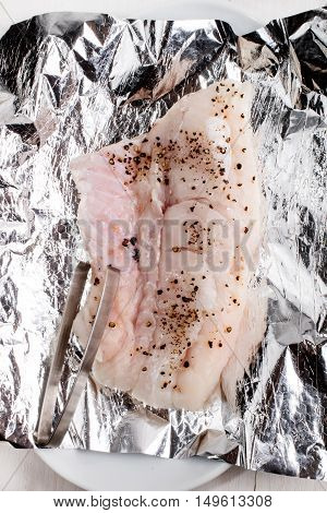 raw hake with crushed black peppercorn on aluminum foil