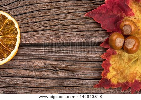 Autumn leaf with filberts and orange over old wooden background with empty space for text