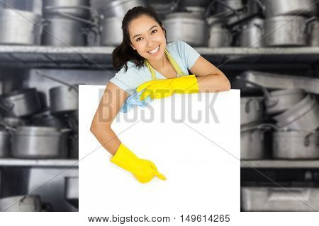 Happy cleaning lady pointing to white surface against shelf full of pans