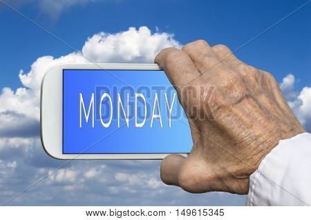Smart phone in old hand with days of the week - Monday on screen. Selective focus.