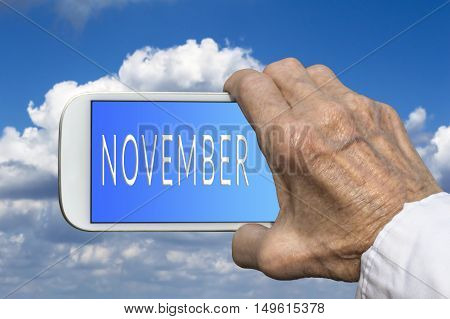 Smart phone in old hand with month of the year - November on screen. Selective focus.