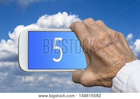 Smart phone in old hand with number FIVE on screen. Selective focus