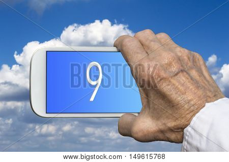 Smart phone in old hand with number NINE on screen. Selective focus