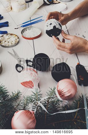 Creative diy hobby. Making handmade craft black stylish christmas balls with lace. Woman's leisure, tools for creating holiday decorations. Female hands closeup working on white wooden table, vertical