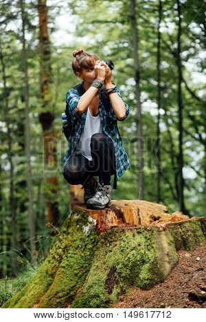 Young Woman Standing In The Middle Of A Forest On A Log