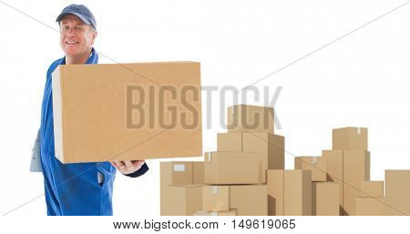 Happy delivery man showing cardboard box against cardboard boxes over white background