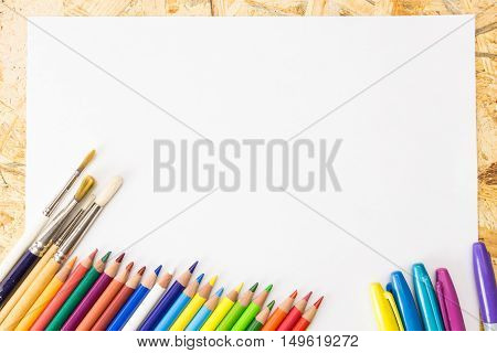 Bunch Of Colorful Pencils, Markers And Paint Brushes, On Blank Sheet Of Paper, On Wooden Surface