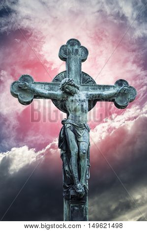 A statue of Jesus Christ crucified against unusual dramatic sky.