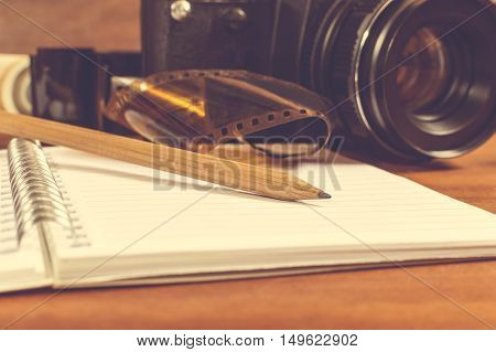 Old SLR camera on the table next to negative film strip and in the foreground a notebook and pencil. Selective focus on pencil.