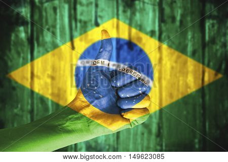 Hand covered in the flag of Brazil.