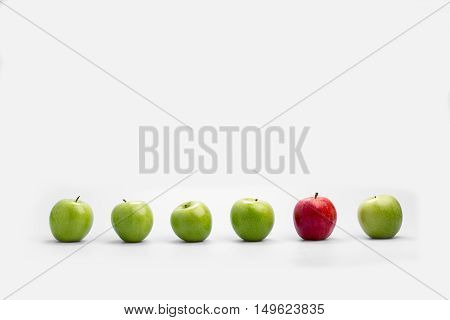 Row of fresh green apples with a single red one isolated on white with copy space conceptual of individualism diversity originality and choice