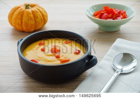 Pumpkin soup with chopped red peppers in a brown ceramic bowl with handles a munchkin pumpkin a bowl with red chopped peppers a grey napkin and a soup spoon on light brown wooden background. Selected focus.
