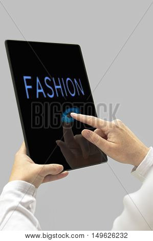 Fashion message on digital tablet computer display. Woman hands with tablet computer. Selective focus.