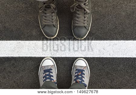 Feet in sneakers standing next to yellow street lines. Shallow depth of field