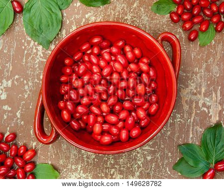 Ripe cornelian cherry in a clay bowl on wooden background