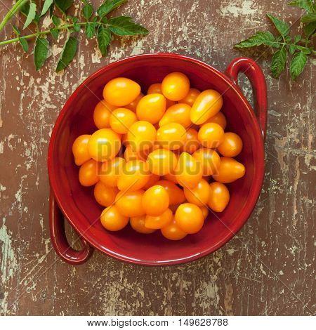 Bowl of sweet yellow pear shaped tomatoes on a rustic wooden table