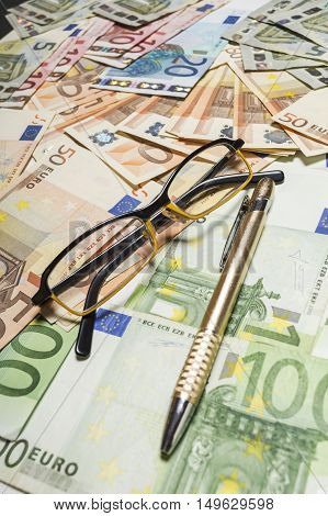 Pen and glasses with euro banknotes. Shallow depth of field