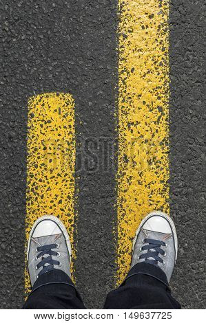 Gray sneaker shoes standing on yellow line.